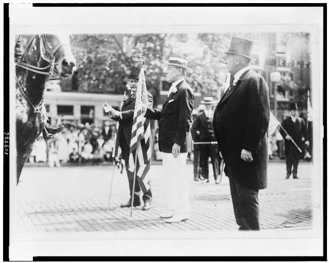 [Woodrow Wilson, holding U.S. flag, in parade, on Preparedness Day, Washington, D.C.]