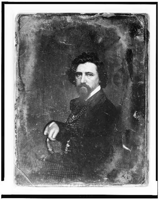 [Unidentified man, half-length portrait, body in profile to left, facing front, with beard]