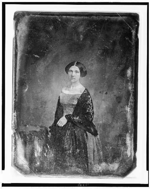 [Unidentified woman, about 35 years of age, three-quarter length portrait, three-quarters to the left, facing front, standing beside table with tablecloth and open book,]