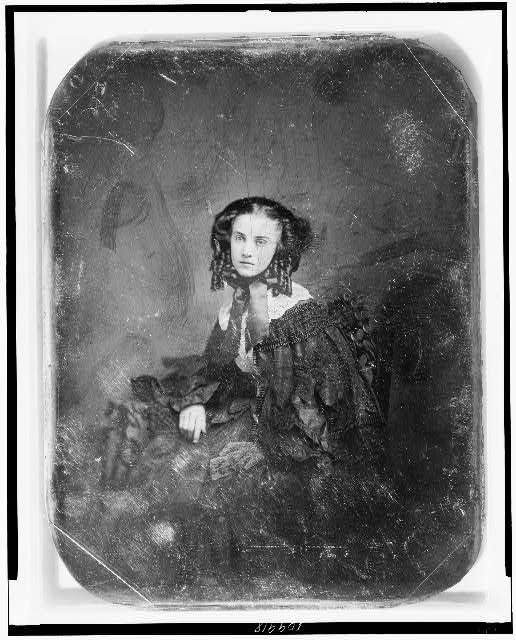 [Unidentified woman, about 20 years of age, three-quarter length portrait, three-quarters to the left, seated in chair beside small table with tablecloth, wearing bonnet and cape]