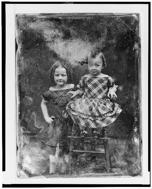 [Two unidentified girls, about three and five years of age, the younger child seated in high chair, older one standing beside her on left, both nearly facing front]
