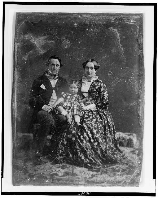 [Unidentified man and woman, both about 30 years of age, with a child about two years of age seated on woman&#39;s knee, full-length portraits, facing front, seated on chairs on carpet]