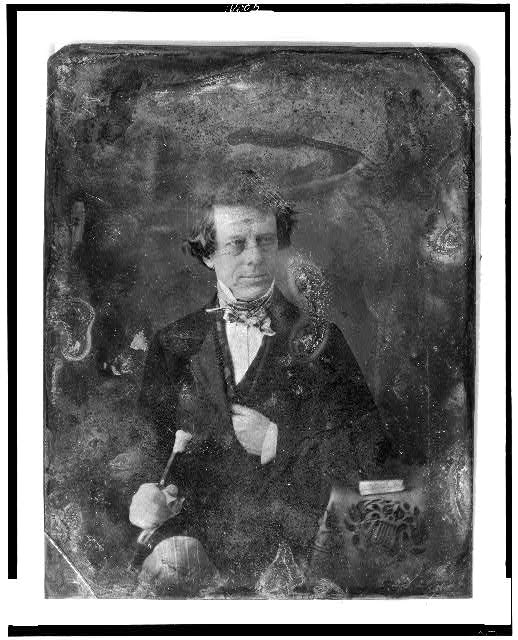 [Henry Inman with walking stick, half-length portrait, facing three-quarters to the right, seated, with a book on a small table covered with a tablecloth showing lyre ornament]