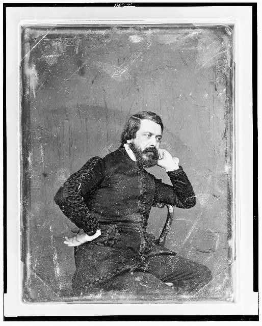 [Unidentified man, three-quarter length portrait, three-quarters to the right, seated, with arm over back of chair, hand to cheek, with full beard, wearing jacket with elaborate trimming]