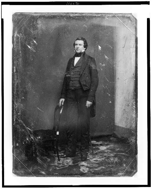 [Alexander Hugh Holmes Stuart, full-length portrait, standing slightly to the left, one hand resting on the back of a chair; studio background showing prominently]
