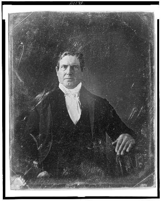 [Unidentified man, about 40 years of age, half-length portrait, facing front, seated with hand on table]