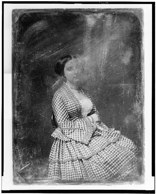 [Unidentified woman, about 25 years of age, three-quarter length portrait, three-quarters to the right, seated in chair, wearing plaid dress]