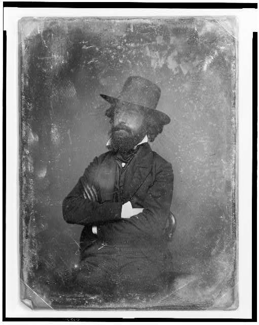 [Unidentified man, three-quarter length portrait, facing left, sitting in chair, wearing hat and a dark glove on one hand]