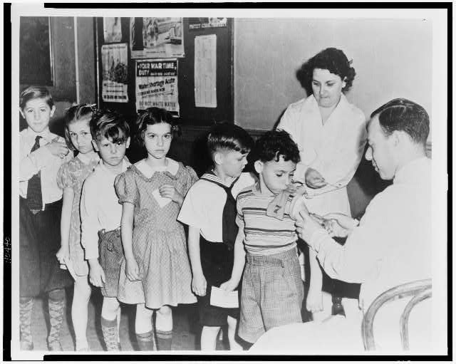 Health in a U.S. city - a serum and vaccine farm. Children await inoculation