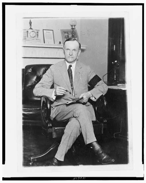 [Calvin Coolidge, full-length portrait, seated at desk, facing front, holding pen and paper, wearing black armband in mourning for President Harding]