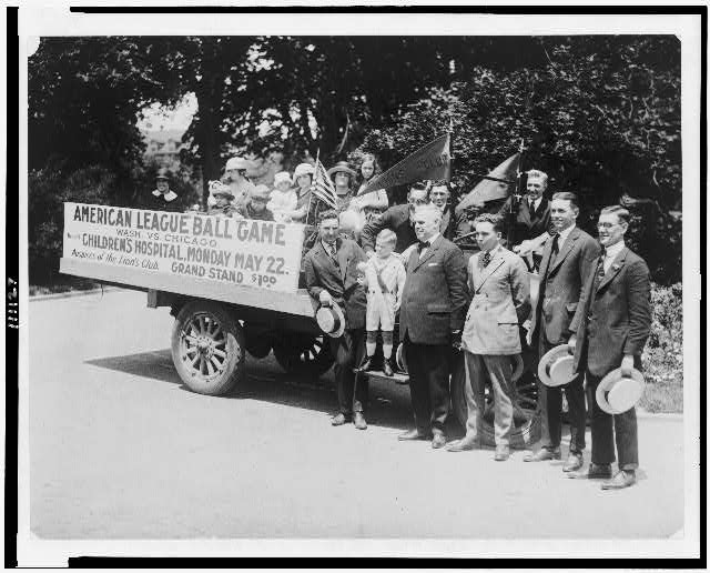 "[Group of people on and around truck, with sign, ""American league ball game, Wash. vs. Chicago, benefit Children's Hospital, ...""]"