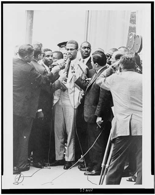 [Malcolm X, full-length portrait, standing, facing slightly left, being interviewed by reporters]