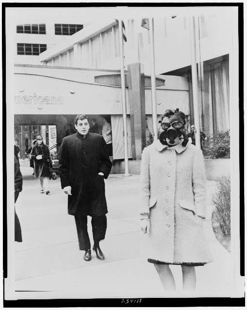 [Woman wearing gas mask outside of Americana hotel]