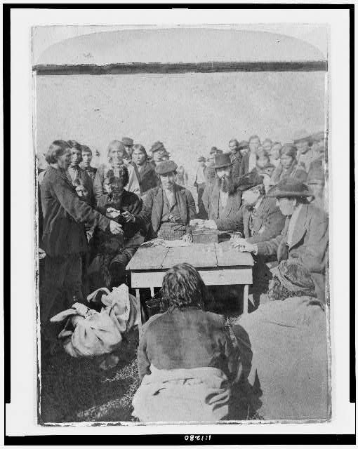 [Cherokee payments(?). Several men seated around table counting coins; large group of Native Americans stand in background]