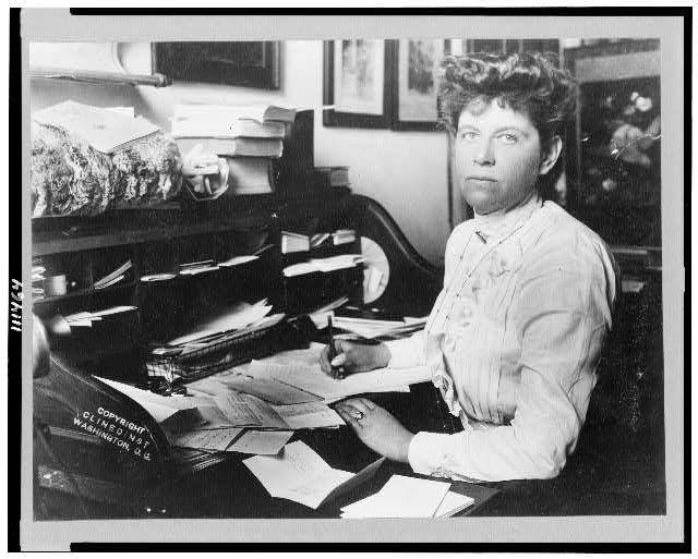 [Mabel Boardman, half-length portrait, seated at desk, facing left, with pen in hand]