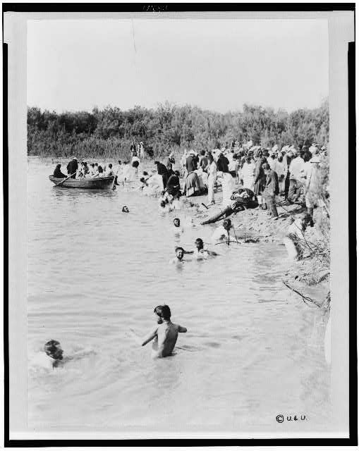 [Pilgrims bathing in the Jordan River, after the water has been blessed by priest of the Greek Orthodox Church]