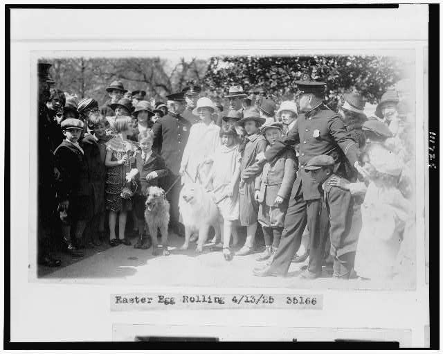 [Mrs. Coolidge with two dogs, policemen, and children at Easter egg roll]