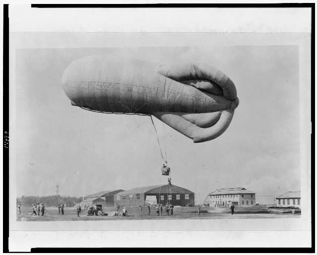 "[""Pilot"" climbing up rope to get into basket (gondola) suspended below observation kite balloon during training at the U.S. Naval Air Station, Hampton Roads, Virginia]"