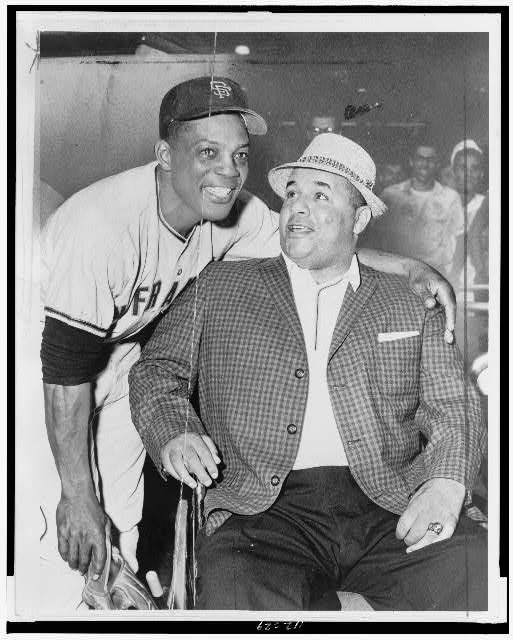 [Willie Mays, standing, wearing baseball uniform, with arm around shoulders of Roy Campanella, seated]