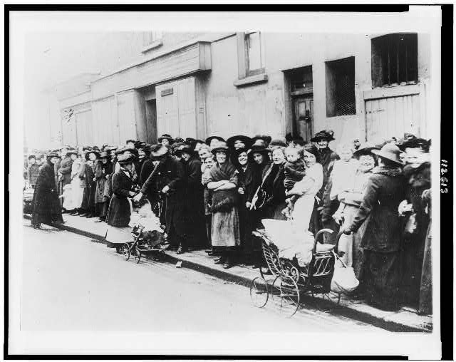 [Women and children wait in a bread line in England]