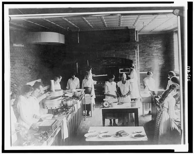 [Women canning food in industrial kitchen in a school(?) during war]