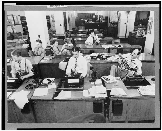 New York, New York. Newsroom of the New York Times newspaper. Reporters and rewrite men writing stories, and waiting to be sent out. Rewrite man in background gets the story on the phone from reporter outside