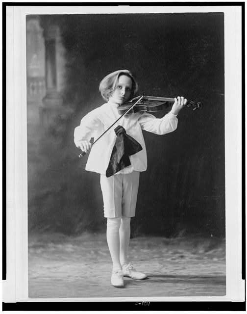 [Boy, standing, full-length, facing slightly right, playing violin]