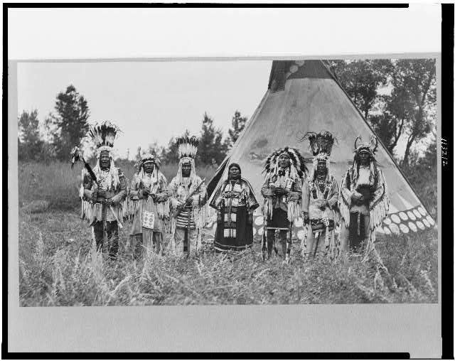 [Group of Siksika (Blackfeet) men and one woman singing in front of tipi]