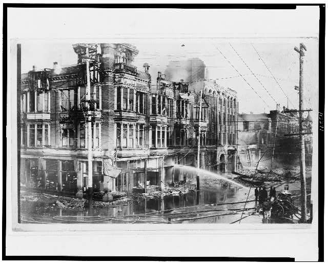 [Block of burned buildings in San Francisco after the 1906 earthquake with fire truck spraying water on them]