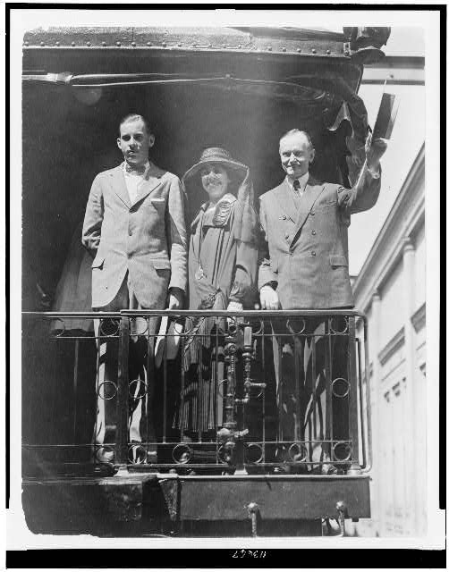 [President Calvin Coolidge, full-length portrait, standing, facing slightly left, with wife and son, on back of railroad train]
