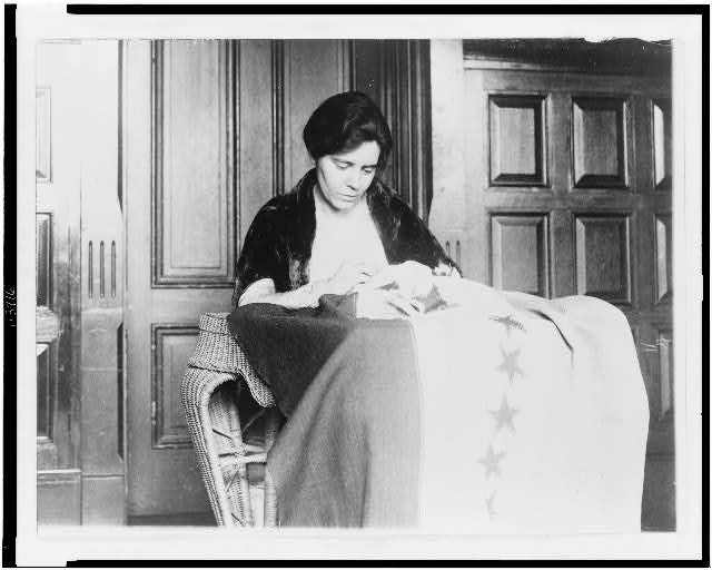 Miss Alice Pavl is shown sewing the thirty-sixth star on the suffrage ratification banner, the stars having been added from time to time as the various states ratified
