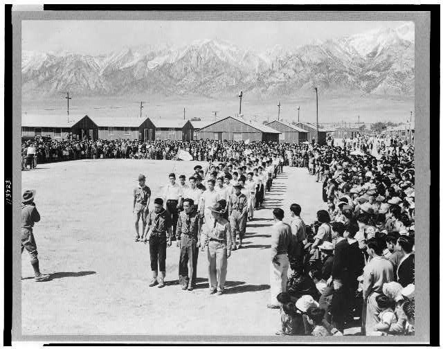 Evacuees of Japanese ancestry attending Memorial Day services at Manzanar, California, a War Relocation authority center--Boy Scouts and American Legion members participating in the services appear in the foreground ...