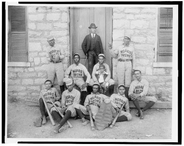 [African American baseball players from Morris Brown College, with boy and another man standing at door, Atlanta, Georgia]