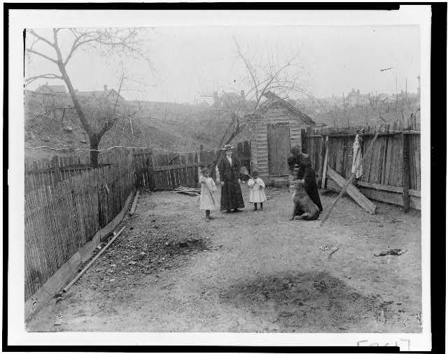 [Two African American women with two girls and a dog in backyard(?)]