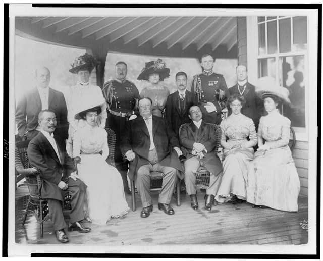 [William H. Taft, seated on porch, with group of women and men]