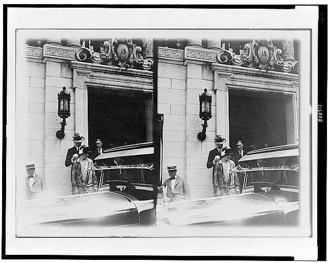[Mr. and Mrs. Charles A. Lindbergh standing in front of building in the Washington, D.C. area, with automobile in foreground]