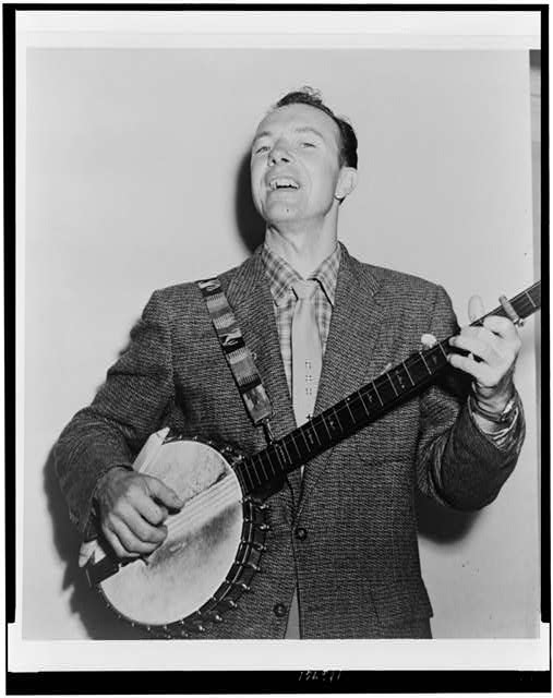 [Pete Seeger, half-length portrait, singing while playing banjo]
