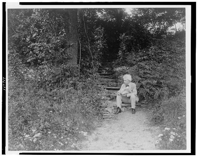 [Mark Twain, full-length portrait, facing left, seated on step, outdoors, holding cigar]