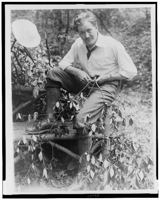 [John Charles Thomas, singer, full-length portrait, sitting on log bench, whittling a small branch]