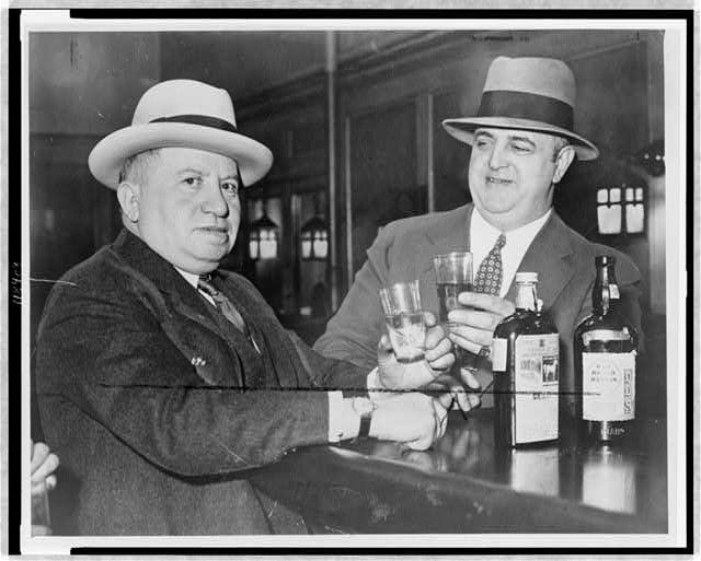 Izzy Einstein (l) sharing a toast with Moe Smith in a New York bar]