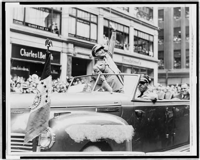 [General Dwight D. Eisenhower waves from automobile in parade to people in buildings above]