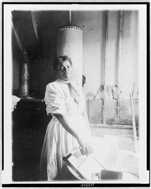 [African American woman, three-quarter length portrait, standing, facing front, doing laundry at wash tub, in Washington, D.C. or New York]