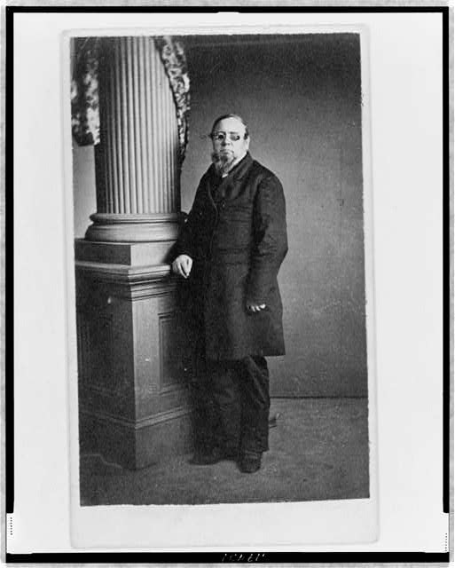 [Unidentified man, full-length portrait, wearing spectacles with colored lenses, standing next to column, facing left]