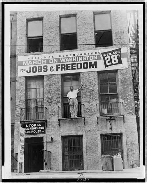 [Cleveland Robinson, full-length portrait, facing front, standing on second floor balcony of the National Headquarters of the March on Washington in Harlem, with his arm lifted up toward banner announcing the march]