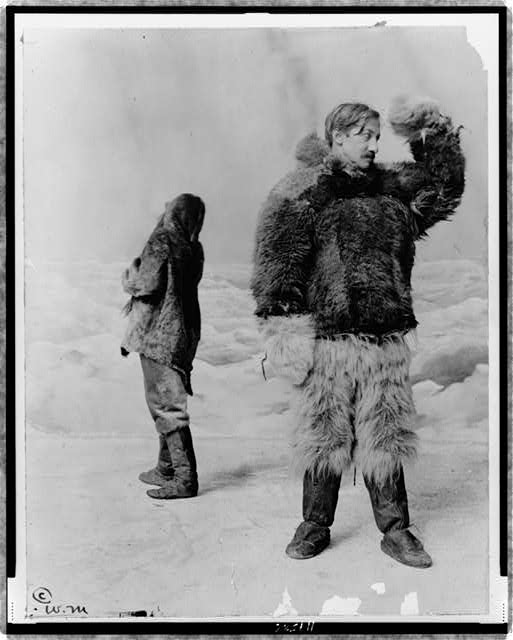 "[Frederick Albert Cook, full-length portrait, standing, facing right, wearing fur clothing, in front of ""arctic"" backdrop, with another man standing behind him]"