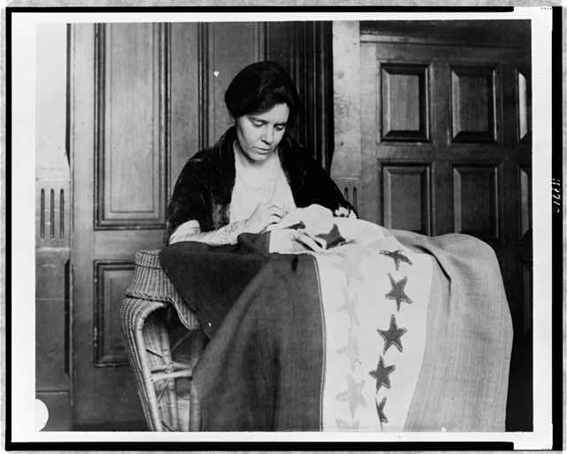 [Alice Paul, half-length portrait, seated, facing slightly right, sewing suffrage flag]