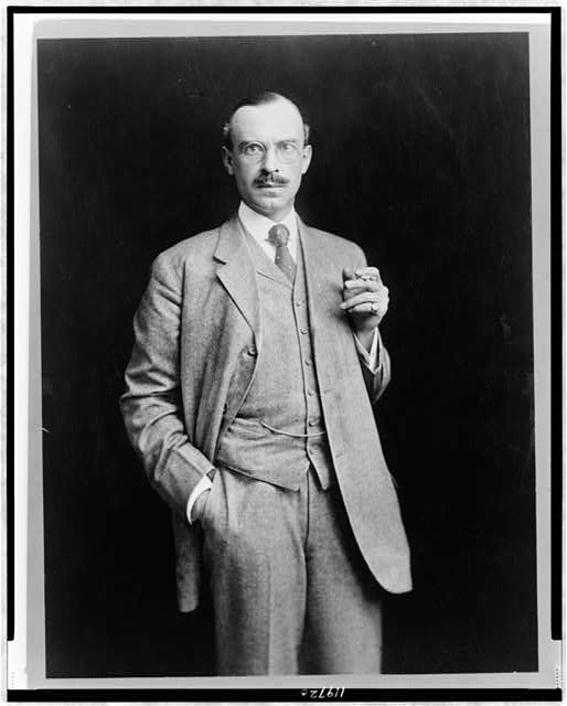 [John Barry Ryan, three-quarter length portrait, standing, facing front, holding cigarette]