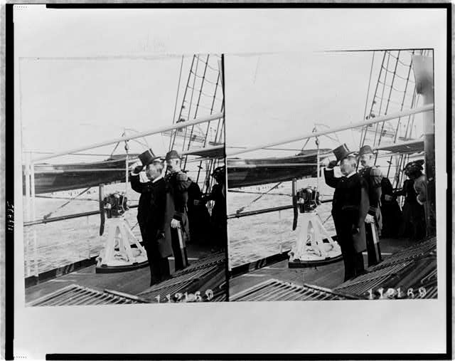 [Theodore Roosevelt, full-length portrait, facing left, standing on deck of ship, with a naval officer]