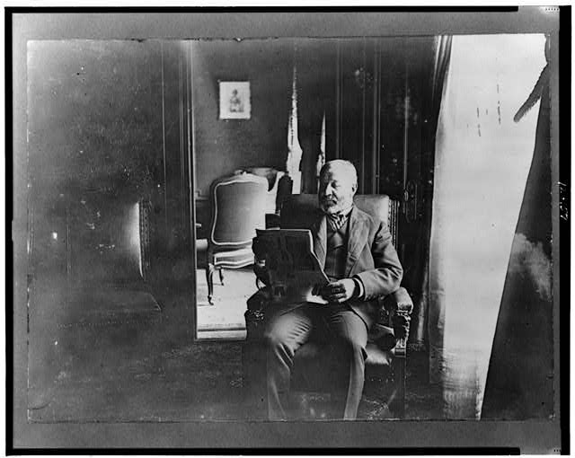 [Richard Croker, three-quarter length portrait, seated, reading newspaper, facing left]