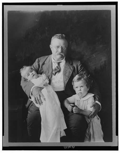 [Theodore Roosevelt, three-quarter length portrait, seated, facing slightly right, with Master Richard Derby, and holding Kermit Roosevelt, Jr.]